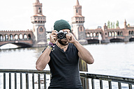 Germany, Berlin, man standing in front of Oberbaum taking pictures from viewer - TAMF00704