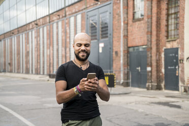 Portrait of smiling man looking at his cell phone - TAMF00716