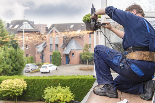 Germany, Craftsman using angle grinder kneeling on balcony - FRF00477
