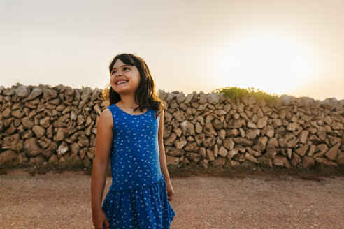 Portrait of happy little girl wearing blue dress at sunset - MGOF02565