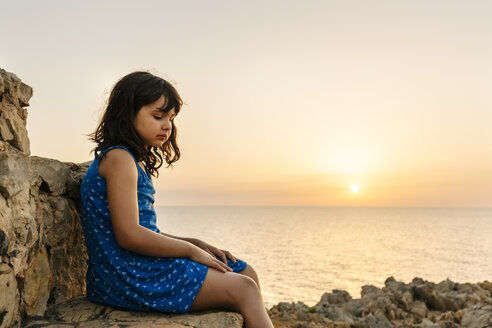 Sad little girl sitting in front of the sea at sunset - MGOF02568