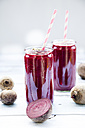 Two glasses of beetroot smoothies with hemp seed and whole and sliced beetroots - LVF05509