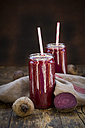 Glasses of beetroot smoothies with hemp seed and whole and sliced beetroot on wood - LVF05512