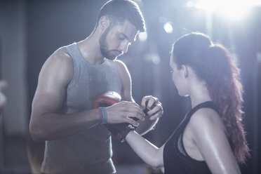 Coach helping female boxer putting on boxing gloves - ZEF11063
