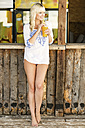 Smiling blond woman with beverage standing in front of a beach hut - GDF01165