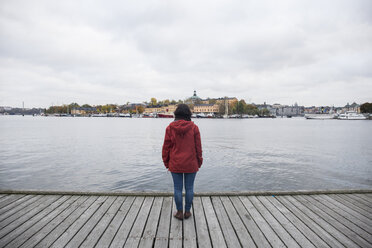 Sweden, Stockholm, back view of woman standing on pier looking at the city - ABZF01438