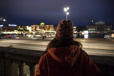 Back view of woman looking to the city by night - ABZF01447
