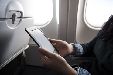 Woman sitting in airplane using E-Book, partial view - ABZF01453