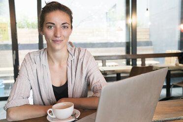Portrait of smiling young woman with cup of coffee and laptop in a coffee shop - TAMF00731