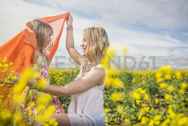 Mother and little daughter playing together in rape field - ZEF11136