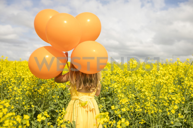 Back view of little girl with orange balloons standing in rape field - ZEF11139