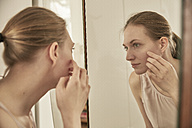 Woman looking in mirror - SUF00084