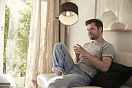Relaxed man at home sitting on couch with cell phone - SUF00087