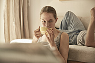 Woman drinking tea in living room with man in background - SUF00093