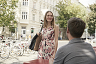 Smiling woman arriving at a sidewalk cafe looking at man - SUF00105