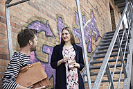 Smiling man with bag looking at woman on stairs - SUF00111