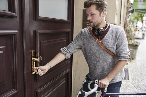 Man with bicycle at front door - SUF00138