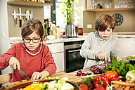 Boy and girl chopping vegetables in the kitchen - TSFF00133