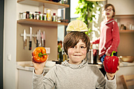 Portrait of smiling boy standing in kitchen with half of white cabbage on his head and bell peppers in hands - TSFF00139