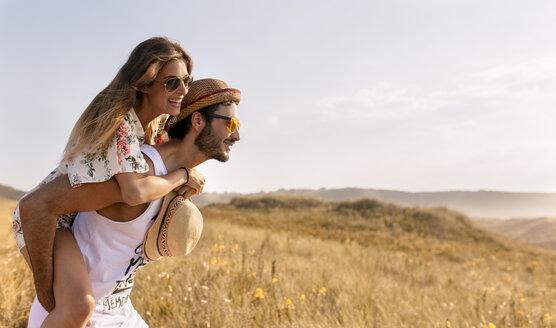 Man giving his girlfriend a piggyback ride in nature - MGOF02578