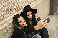 Two best friends pulling funny faces while taking selfie with cell phone - EBSF01860