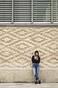 Young woman standing in front of facade looking at cell phone - EBSF01863