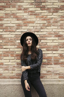Fashionable young woman wearing black hat standing in front of facade - EBSF01866