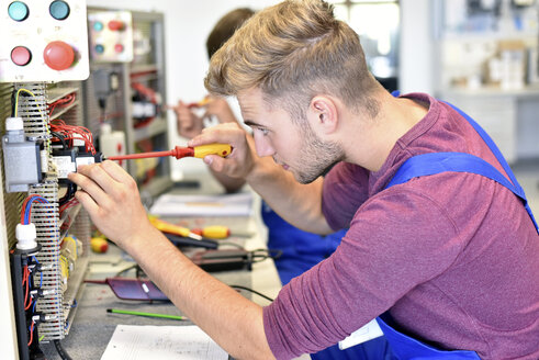 Two electrician students working at electrical panel - LYF00610