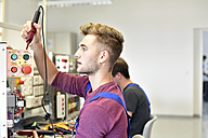 Electrician students looking at device - LYF00613
