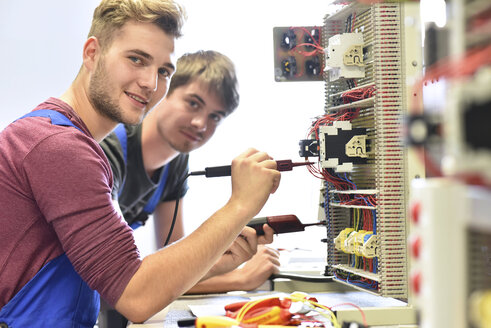 Two electrician students working at electrical panel - LYF00616