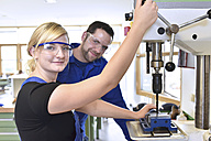 Portrait of smiling instructor with female trainee at drill machine - LYF00628