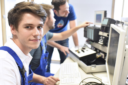 Portrait of smiling student with technical instructor in background - LYF00634