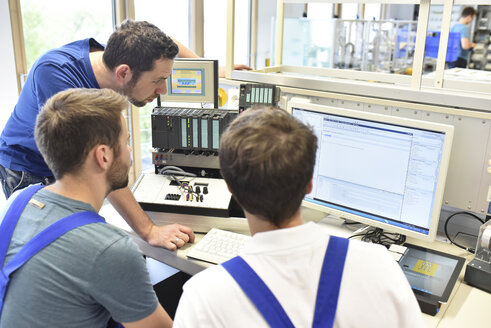 Technical instructor teaching students at computer screen - LYF00637