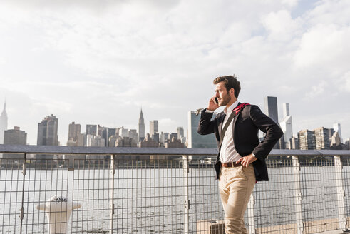 USA, New York City, businessman at East River on cell phone - UUF08845