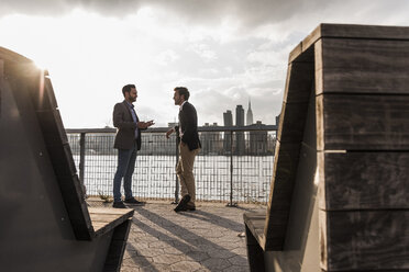 USA, New York City, two businessmen talking at East River - UUF08857