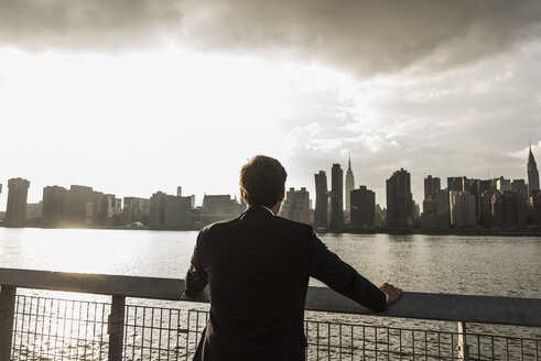 USA, New York City, back view of businessman looking at skyline of Manhattan - UUF08869