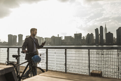 USA, New York City, businessman with bicycle walking along East River looking at cell phone - UUF08872
