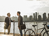 USA, New York City, two businessmen with bicycle at East River - UUF08875