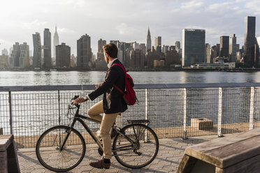 USA, New York City, businessman on bicycle looking at skyline of Manhattan - UUF08884