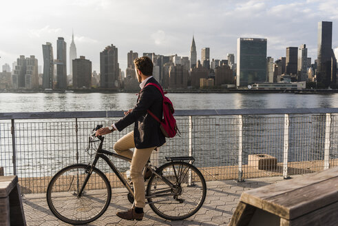 USA, New York City, businessman on bicycle looking at skyline of Manhattan - UUF08884