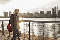 USA, New York City, businessman walking along East River looking at cell phone - UUF08890