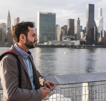 USA, New York City, businessman at East River - UUF08893