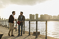 USA, New York City, two young men walking along East River - UUF08899