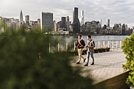 USA, New York City, two young men walking along East River - UUF08905
