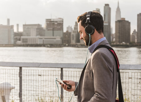 USA, New York City, young man with headphones and cell phone at East River - UUF08911