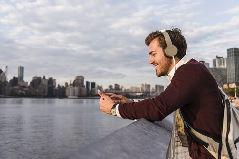 USA, New York City, smiling young man with headphones and cell phone at East River - UUF08914