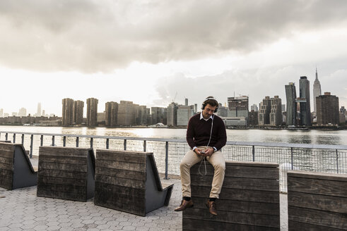 USA, New York City, young man with headphones and cell phone sitting at East River - UUF08917