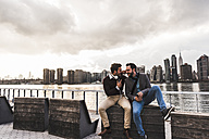 USA, New York City, two happy young men with headphones and cell phone sitting at East River - UUF08920