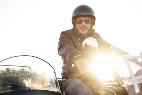 Portrait of cool biker wearing helmet and sunglasses on his sidecar motorcycle at backlight - JASF01262