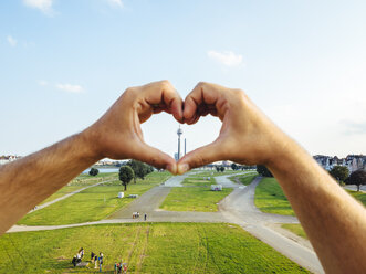 Germany, Duesseldorf, hands forming a heart framing Rhine Tower - KRPF01932